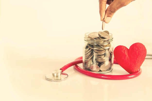Concepto de enfermedad cardíaca de seguro de salud y atención médica, forma de corazón rojo con estetoscopio, atención médica financiera