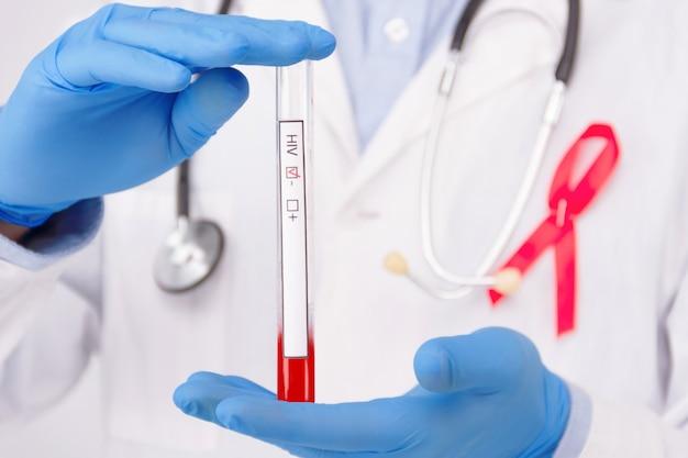 Concepto de enfermedad de sida / vih. doctor con bata blanca y guantes médicos de goma azul con cinta roja fijada como símbolo de ayudas.