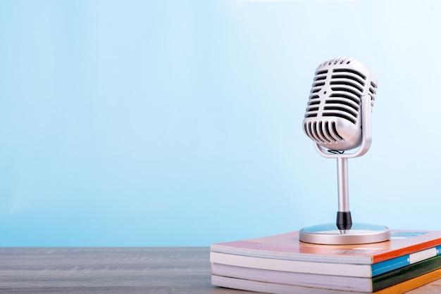 Concepto de enseñanza de la educación: el micrófono retro con muchos libros puso en la tabla de madera aislada en fondo azul.