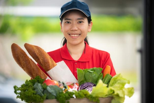 Concepto de entrega de alimentos y servicio de mensajería, el personal de entrega en uniforme está trabajando actualmente para entregar alimentos y productos frescos a la casa del cliente, recibir pedidos a través de pedidos en línea