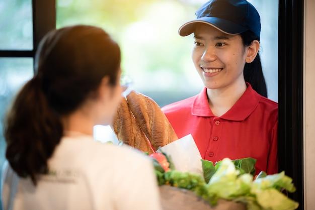 Concepto de entrega de alimentos y servicio de mensajería, el personal de entrega en uniforme está trabajando actualmente para entregar alimentos y productos frescos a la casa del cliente.