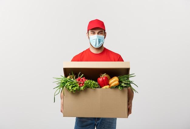 Concepto de entrega: apuesto hombre de mensajería de entrega de comestibles caucásico en uniforme rojo y mascarilla con caja de supermercado con frutas y verduras frescas