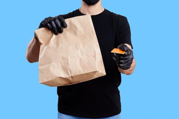 Concepto de entrega de comida. mensajero en uniforme negro sostenga la bolsa de papel con comida para llevar sobre fondo azul.