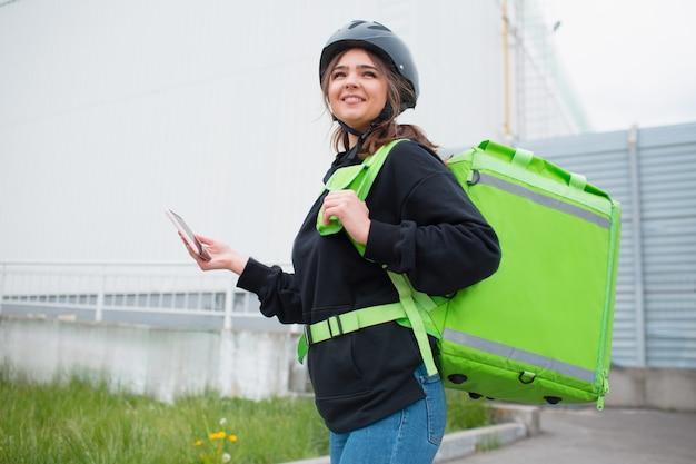 Concepto de entrega de comida. la repartidora de alimentos tiene una mochila nevera verde. ella quiere entregar más rápido y llegar a los clientes. ella nos trajo comida