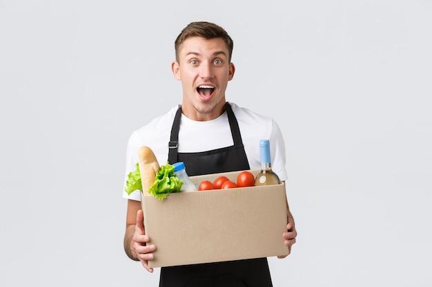Concepto de entrega y compras de comestibles al por menor vendedor emocionado anuncia una caja de tenencia de promoción impresionante con ...