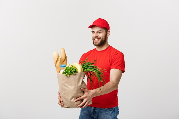 Concepto de entrega: guapo repartidor de cacasian llevando una bolsa de comida y bebida