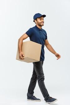 Concepto de entrega - hombre de entrega afroamericano hermoso. aislado en el estudio de fondo gris. espacio de la copia.