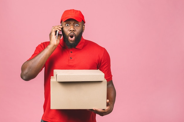Concepto de entrega. hombre negro afroamericano de entrega que lleva el paquete. usando el teléfono.