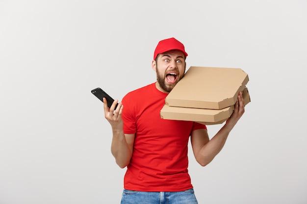 Concepto de entrega: repartidor de pizza guapo hablando al móvil con impactante expresión facial.