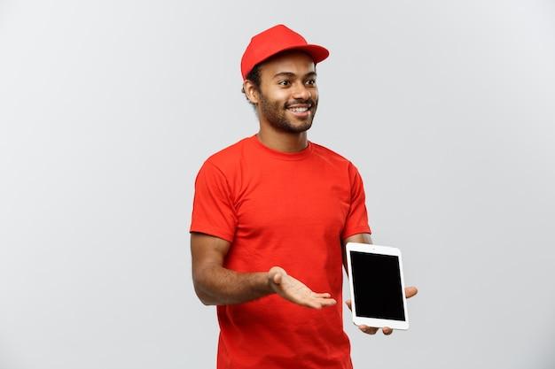Concepto de entrega - retrato de hermoso african american hombre de entrega o mensajero con cuadro que muestra la tableta sobre usted para comprobar la orden. aislado en el estudio de fondo gris. espacio de la copia.