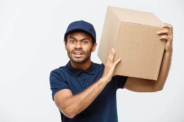 Concepto de entrega - retrato de serio hombre de entrega de african american mostrando expresión tonta agresiva con la celebración de un paquete de caja. aislado en el estudio de fondo gris. espacio de la copia.