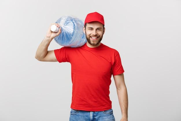 Concepto de entrega: retrato de sonriente mensajero de entrega de agua embotellada en camiseta roja