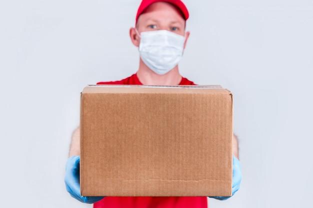 El concepto de entrega segura. un mensajero con un uniforme rojo y una máscara médica protectora y guantes sostiene una caja de cartón, entrega de pedidos sin contacto
