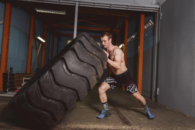 Concepto del entrenamiento del deporte de crossfit - hombre que mueve de un tirón el neumático.