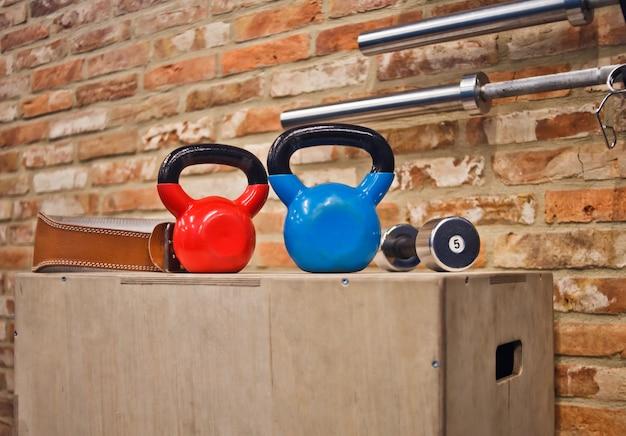 Concepto de entrenamiento funcional. kettlebell, mancuernas de pie en caja de madera contra la pared de ladrillo. equipo de entrenamiento