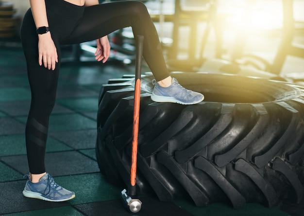 Concepto de entrenamiento funcional. tiempo de un descanso. foto recortada de piernas femeninas, rueda grande, martillo en el gimnasio.