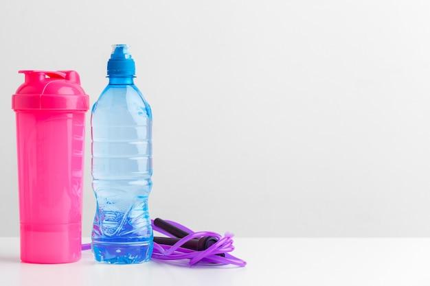 Concepto de entrenamiento y refresco. deportes y salud. botella o agua fresca cerca de la cuerda de saltar