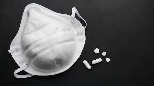 Concepto de epidemia y virus - píldoras blancas y máscaras sobre fondo negro