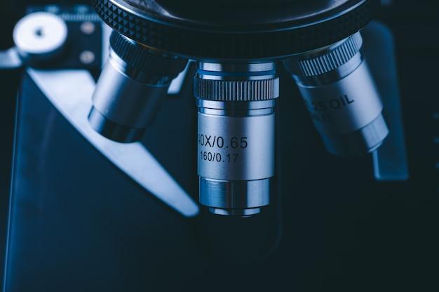 El concepto de equipo de laboratorio médico moderno, cerca de lentes objetivas de un microscopio