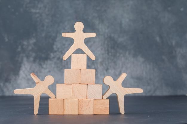 Concepto de equipo y negocio con bloques de madera como pirámide con figuras humanas de madera.