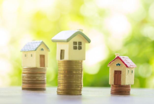 Concepto de escalera de propiedad, casa y pila de monedas para ahorrar para comprar una casa