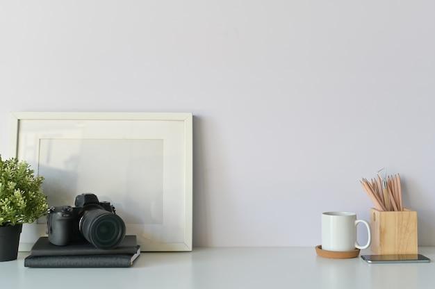 Concepto de escritorio del fotógrafo. mesa de diseñadores, cámara, café y marco de fotos. copia espacio.