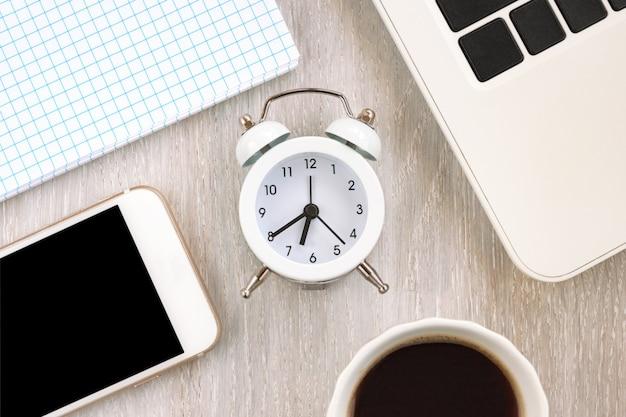 Concepto de escritorio de oficina en casa. ordenador portátil, portátil, smartphone, bloc de notas en blanco, reloj, taza de café en la mesa de madera blanca de cerca. enfoque selectivo. copie el espacio. vista superior. endecha plana.
