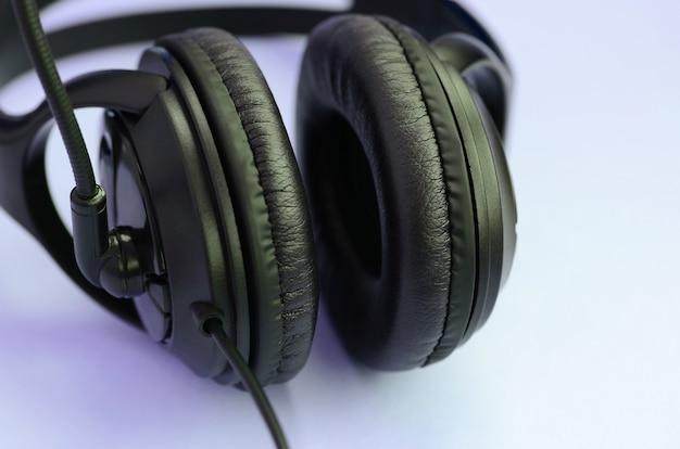 Concepto de escuchar música. auriculares negros se encuentra en el fondo violeta