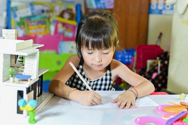 Concepto de escuela en casa, niños asiáticos haciendo la tarea escolar en casa