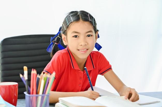 Concepto de escuela en casa, niños asiáticos haciendo tareas escolares en casa