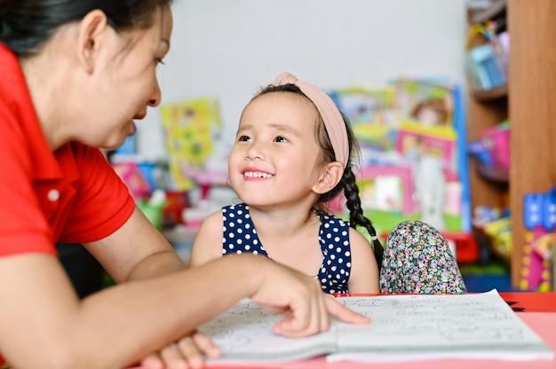 Concepto de escuela en casa, niños asiáticos y madre enseñan a hacer la tarea escolar