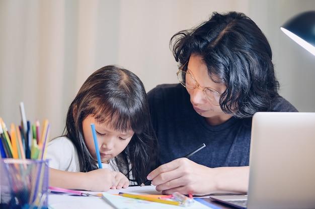 Concepto de escuela en casa, padre enseña a hija a niños asiáticos a hacer tareas escolares y su computadora portátil de uso hace horas extras en la mesa de trabajo en casa por la noche