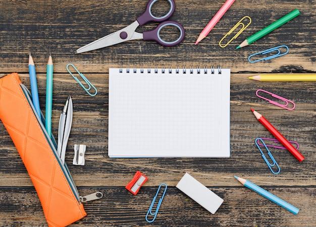 Concepto de escuela con cuaderno, útiles escolares en mesa de madera plana lay.