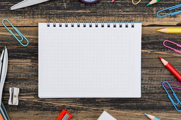 Concepto de escuela con cuaderno, útiles escolares en primer plano de la mesa de madera.