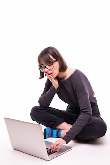 Concepto de escuela, educación, internet y tecnología - joven adolescente sentada en el suelo con ordenador portátil