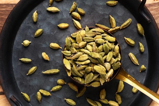 Concepto de especias de alimentos cardamomo o vaina de cardamomo en taza de cobre con espacio de copia