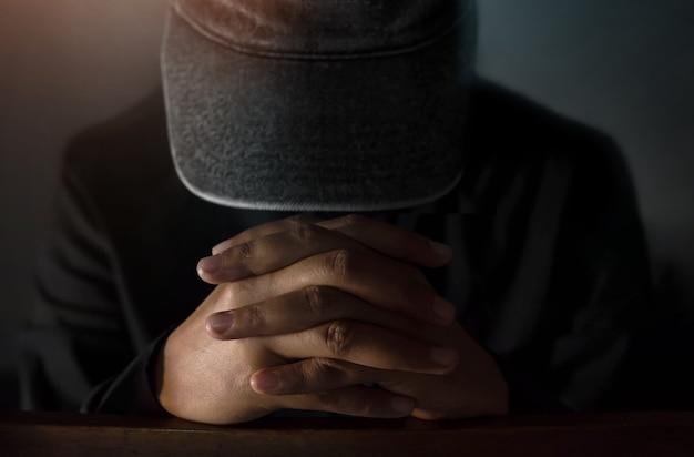 Concepto de esperanza y religión, misterioso hombre esperanzado en sombrero haciendo manos para orar en el da