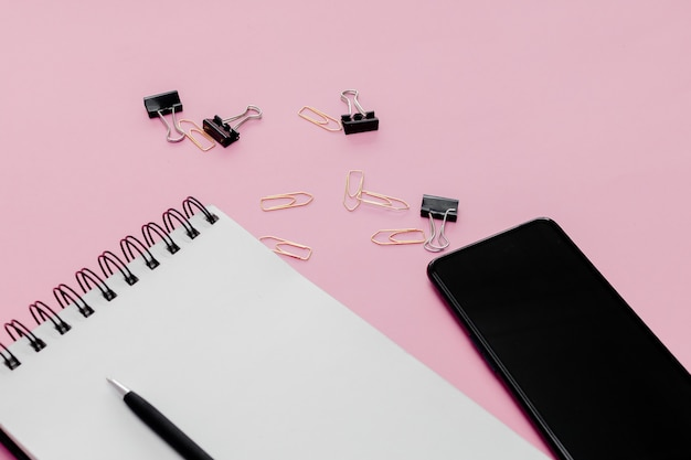 Concepto estacionario, lápiz, bolígrafo y bloc de notas en una tabla abstracta rosa