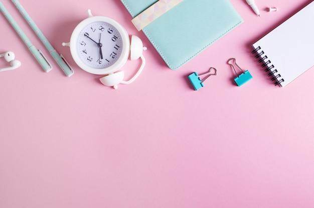 Concepto estacionario, vista superior plano lay foto de lápices, sujetapapeles, despertador, blocs de notas, en blanco y azul sobre fondo rosa con espacio de copia.