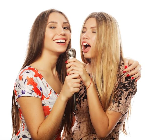 Concepto de estilo de vida, felicidad, emocional y personas: dos chicas de belleza con un micrófono cantando y divirtiéndose
