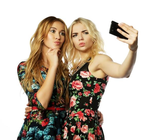 Concepto de estilo de vida, felicidad, emocional y personas. dos mujeres jóvenes tomando selfie con teléfono móvil