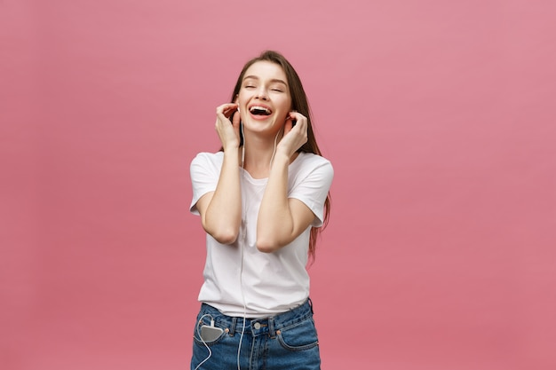 Concepto de estilo de vida. mujer joven que usa el teléfono para escuchar música en fondo rosado