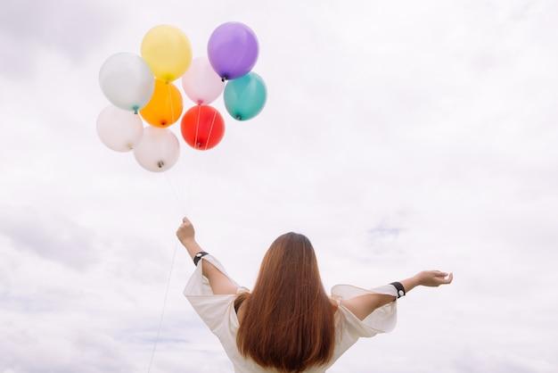 Concepto de estilo de vida de mujer - mano de mujer sosteniendo un montón de globos de colores con cielo azul. estilo del color del filtro del tono de la vendimia.