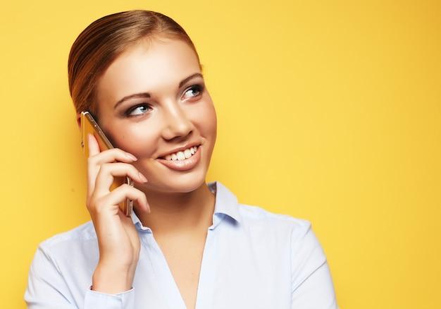 Concepto de estilo de vida, negocios y personas: retrato de mujer de negocios sonriente teléfono hablando sobre espacio amarillo