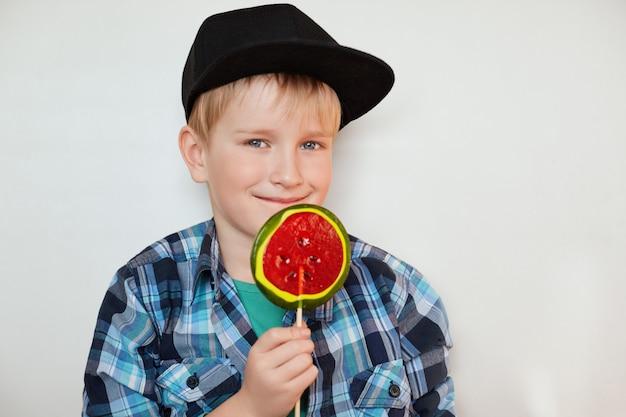 Concepto de estilo de vida y personas. adorable niño varón con ojos azules y cabello rubio con gorra negra y camisa a cuadros posando con dulces