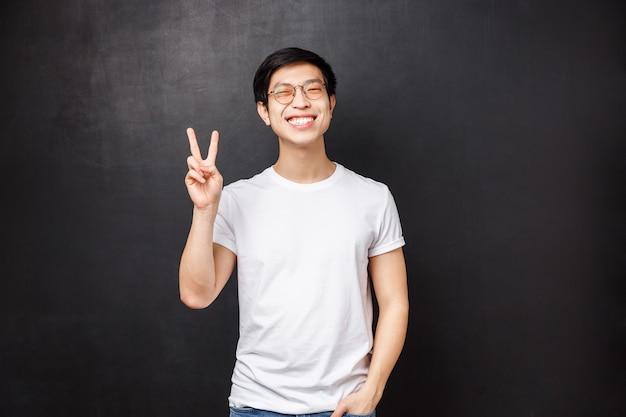 Concepto de estilo de vida y personas. chico asiático positivo feliz con una sonrisa blanca radiante que muestra el signo de la paz, disfrutar divirtiéndose y entretenerse, visitar cursos de formación de equipos, dejar una crítica positiva