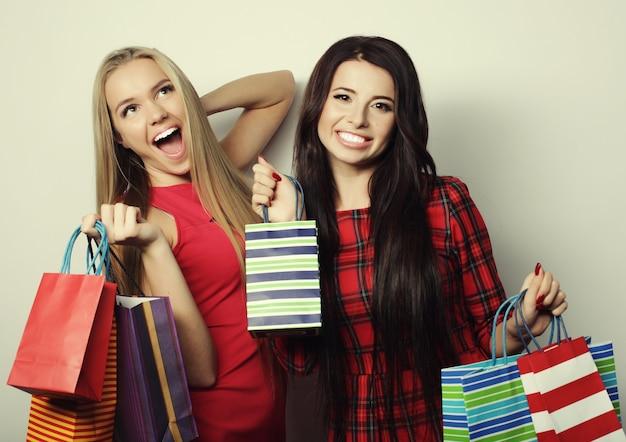 Concepto de estilo de vida y personas: dos mujeres jóvenes con vestido rojo con bolsas de la compra. gran venta.