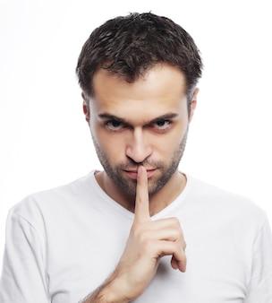 Concepto de estilo de vida y personas: hombre joven con camiseta blanca haciendo gesto de silencio, ¡shhhhh!