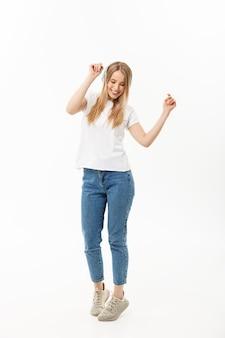 Concepto de estilo de vida: retrato de una estudiante alegre y feliz escuchando música con auriculares mientras baila aislado sobre fondo blanco.