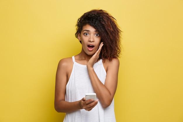 Concepto de estilo de vida - retrato de hermosa mujer afroamericana sorprendente con algo en el teléfono móvil. fondo amarillo pastel del estudio. espacio de la copia.